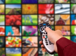 TV Advertising with Cable Commercials Works Shown By Viewer Clicking Remote Toward Busy TV Screen