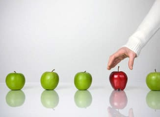 Market Strategy Buying Behavior represented by hand choosing a red apple instead of green apples