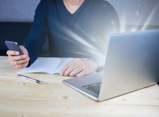 Person sitting at a desk with his phone in hand, seeming to check on his email marketing program on his laptop.