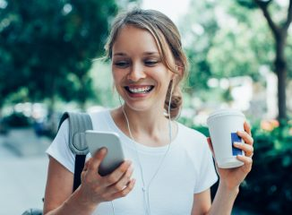SEO Tips represented by closeup portrait of smiling young beautiful woman walking, holding drink, wearing headphones and having video call on smartphone on street