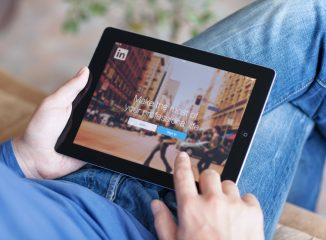 LinkedIn is a social network for search and establishment of business contacts. Here is a photo of a person using a tablet to access a LinkedIn account.