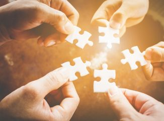 balanced media plan represented by hands connecting jigsaw puzzle pieces
